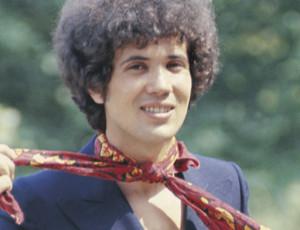 Il cantautore italiano Lucio Battisti si allaccia sorridente un foulard al collo. 1969